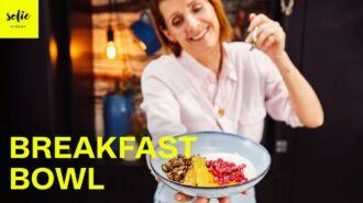 Bol de petit déjeuner avec yaourt, du granola, orange et pomme grenade